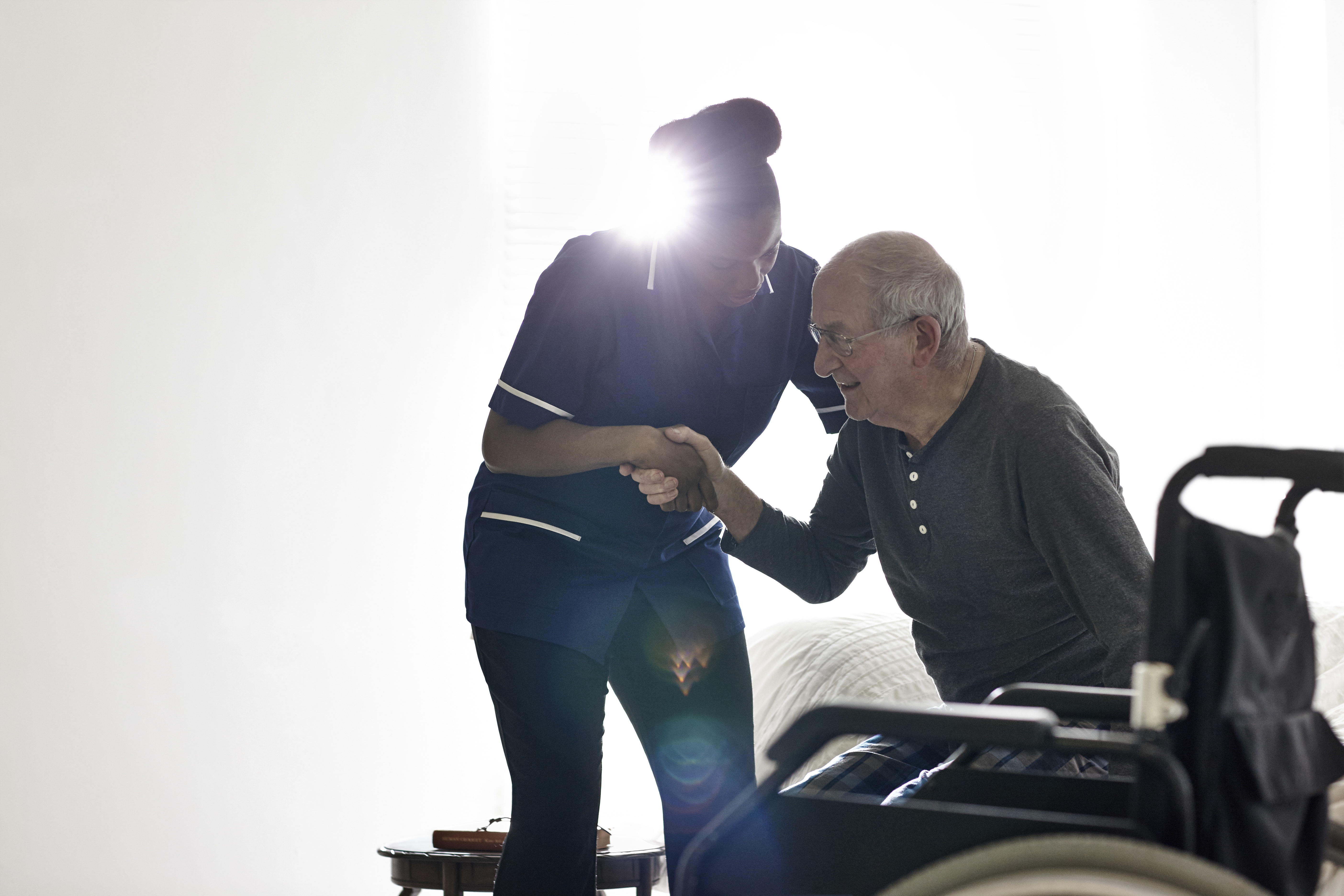 Female nurse helping senior man get up from bed