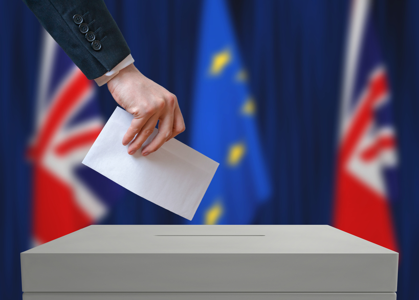Election or referendum in Great Britain. Voter holds envelope.