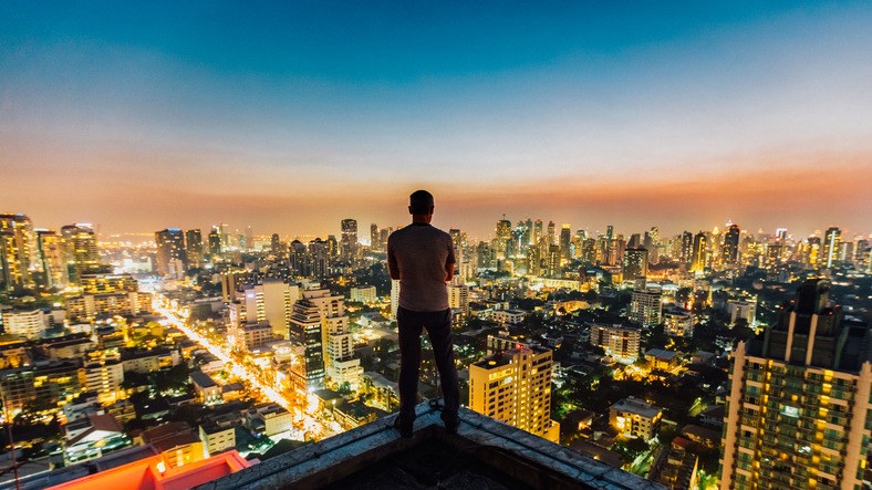man standing on top of a skyscraper view of the Bangkok city skyline.