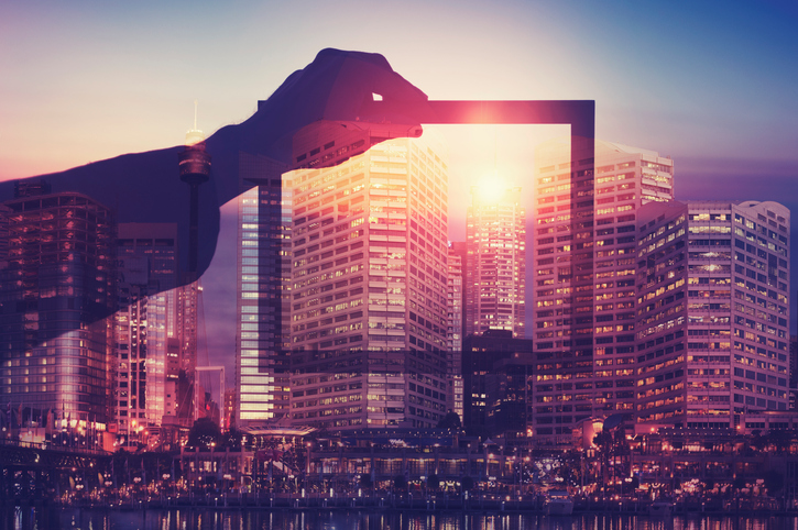 Business man holding a picture frame over city. The man is unrecognizable and you cannot see his face. He is superimposed onto a city skyline at sunset. He is holding a picture looking into the city. Success, vision, innovation concept with copy space.