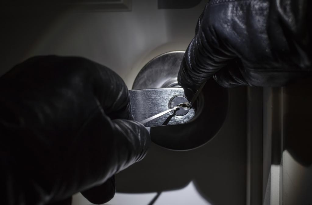 Criminal with black gloves picking lock